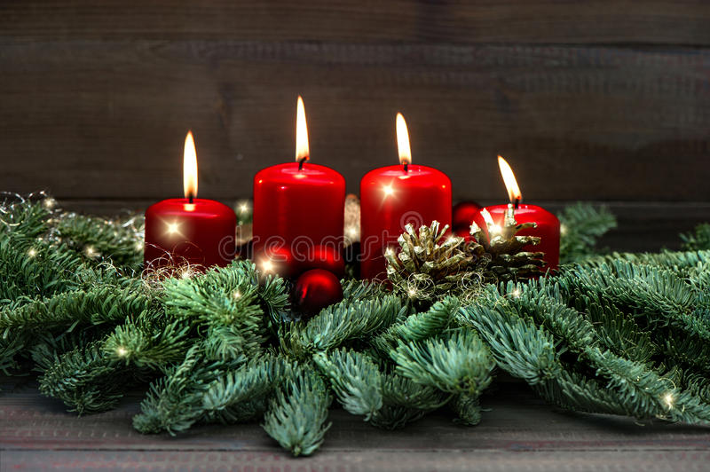 Advent decoration wreath with four red burning candles and light royalty free stock photography