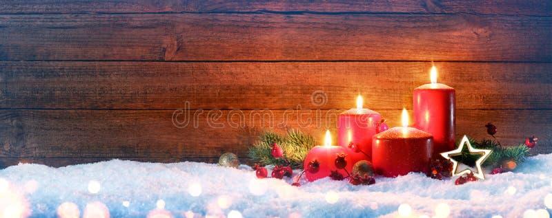 Advent Season - cuatro velas rojas en nieve imagen de archivo