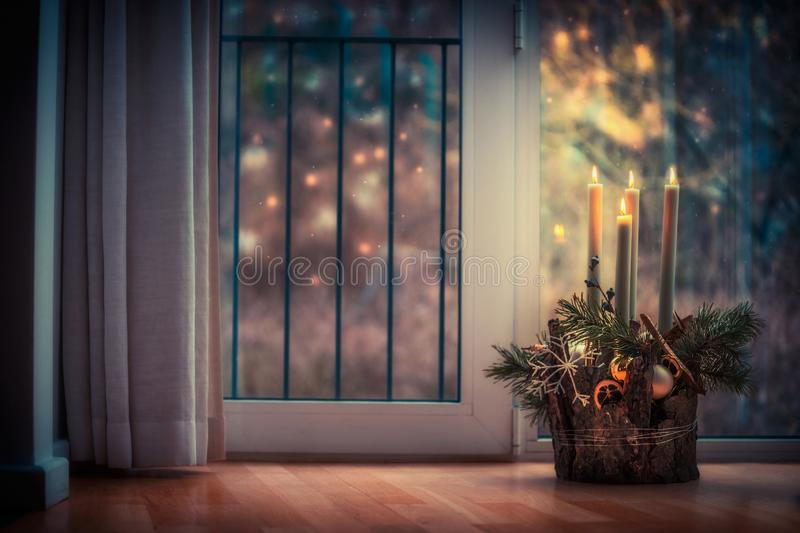 Advent wreath with burning candles at window in dark room. Winter decor interior with warm bokeh lighting. Christmas eve stock photo