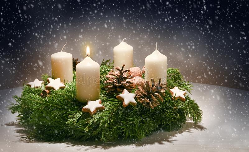 Advent wreath from evergreen branches with white candles, the first is burning for the time before Christmas, dark snowy. Background with copy space, selected royalty free stock image