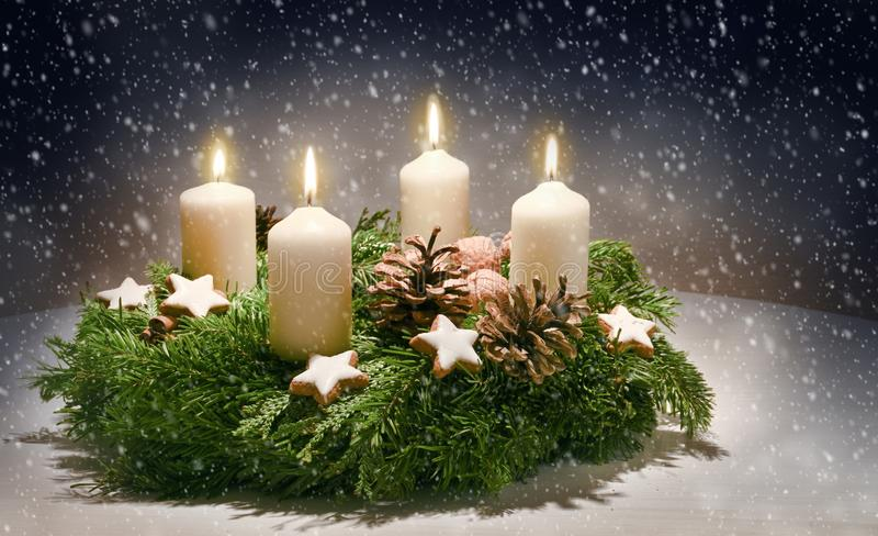 Advent wreath from evergreen branches with white candles, the fourth is burning for the time before Christmas, dark snowy. Background with copy space, selected royalty free stock photos