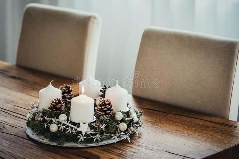 Advent Wreath with four candles on wooden table. White curtains background. Advent Wreath with four candles. The first candle being lit on the first Sunday in stock photography