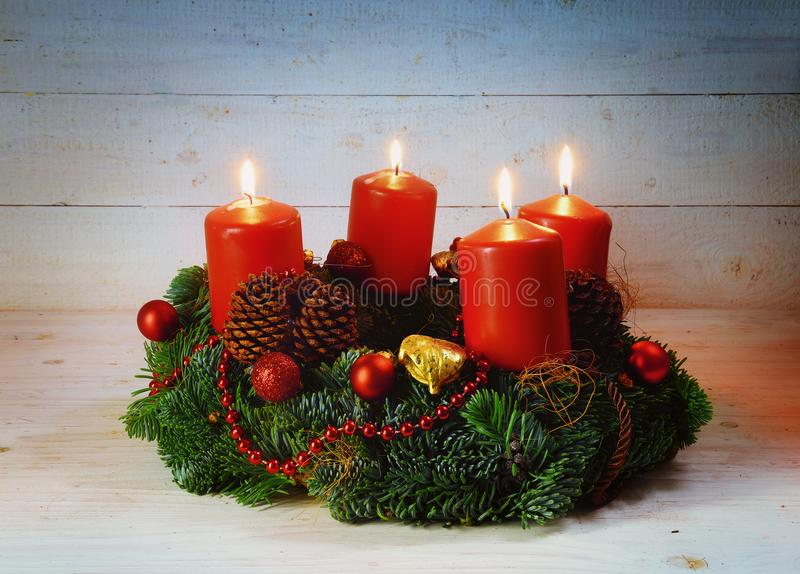 Advent wreath with four red burning candles and christmas decoration on rustic bright wood with copy space, stock photography