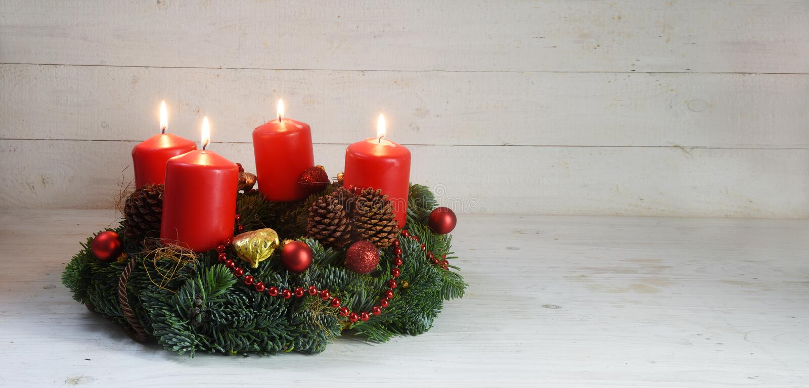 Advent wreath with four red burning candles and christmas decoration on rustic white wood, panorama format with copy space stock image