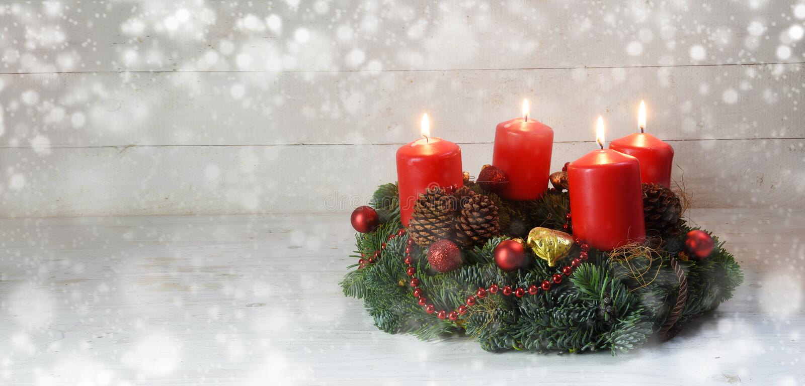 Advent wreath with four red burning candles and christmas decoration on rustic white wood, bokeh lights and blurred stock image