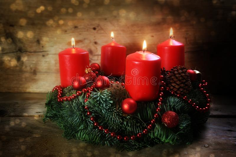 Advent wreath with four red burning candles and christmas decoration on rustic dark wood stock photography