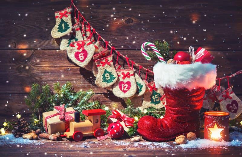 Adventkalender och sko för jultomten` s med gåvor på lantlig träbac arkivfoton