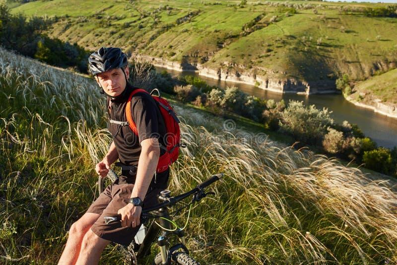 Adventur de la bici de montaña El ciclista tiene un resto en la orilla foto de archivo