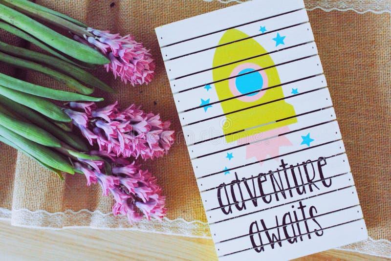 Adventure Awaits Art Work Beside Purple Flowers stock images