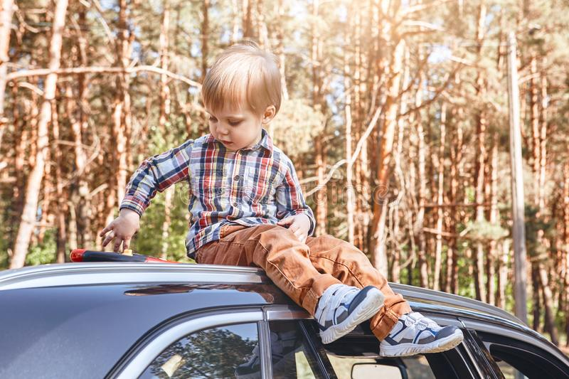 Adventure Awaits. Cute little boy sitting on the car. Family road trip. Portrait of a child sitting on top of a black car and playing with his toy. Forest in the royalty free stock photo