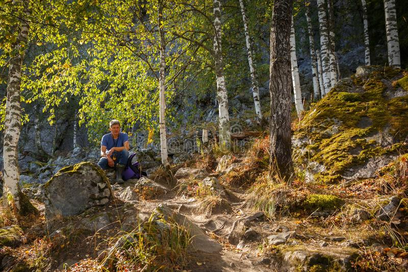 Adventure, backpack, backpacker, beauty, day, discovery, explorer, forest, guide, guy, hand, happy, health, high, hiker, hiking,. The tourist is resting in a stock photography