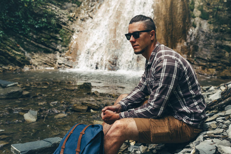 Adventure Backpack Destination Outdoor Leisure Concept. Young man traveler in sunglasses sits on the river bank and inspects sights. Adventure Backpack stock photography