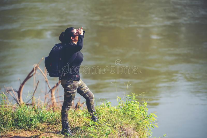 Adventure backpack women standing along the riverside. Adventure backpack woman standing along the riverside looking to the front mountain. Young woman travel royalty free stock photography
