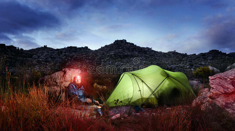Adventure camping tent night. Tent camping wilderness adventure man with headlamp and gas burner in the mountains cooking food at night while looking into stock photo