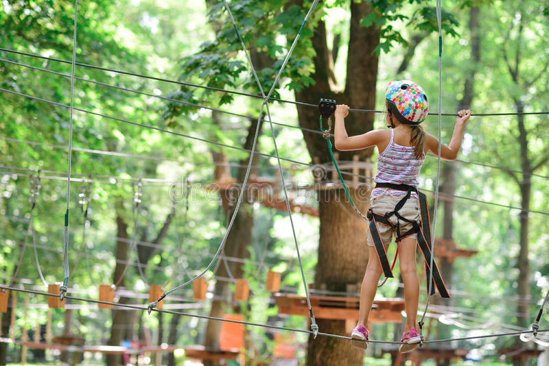 Adventure climbing high wire park - girl on course in mountain stock images