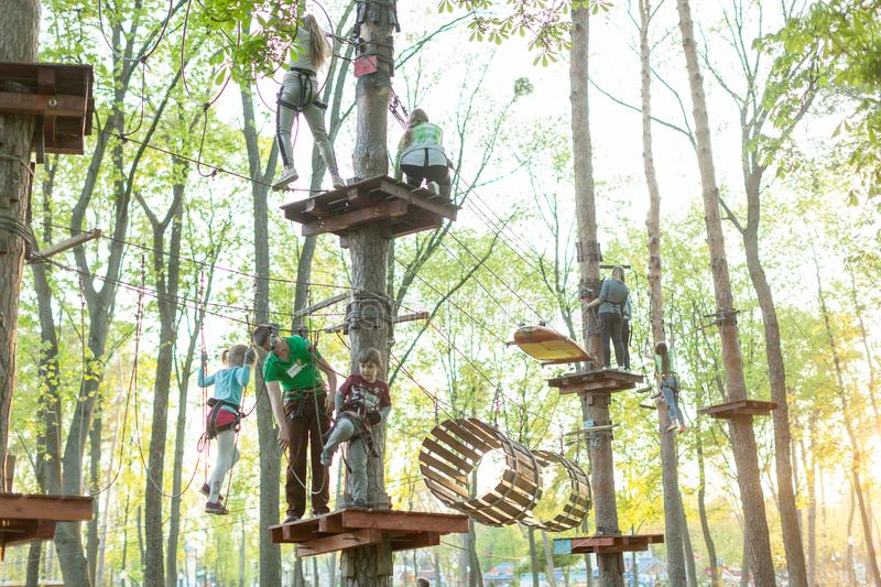 Adventure climbing high wire park - people on course in mountain helmet and safety equipment In The Gorky Park Kharkov Ukraine May stock photo