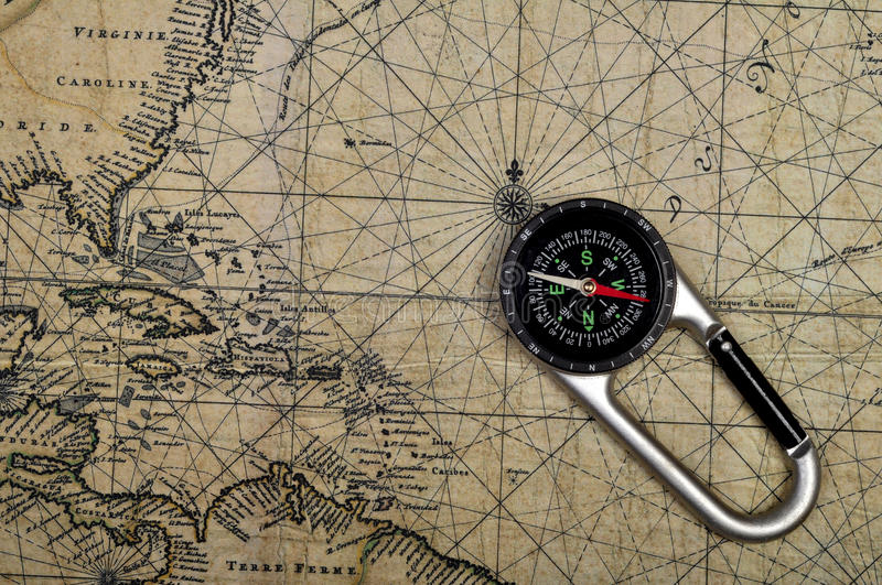 Adventure compass on old maps royalty free stock photos