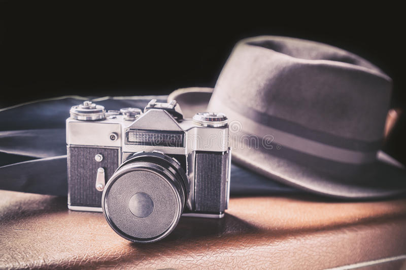 Adventure concept. Old film camera with vintage hat and umbrella on old brown suitcase. Vintage toned stock photography