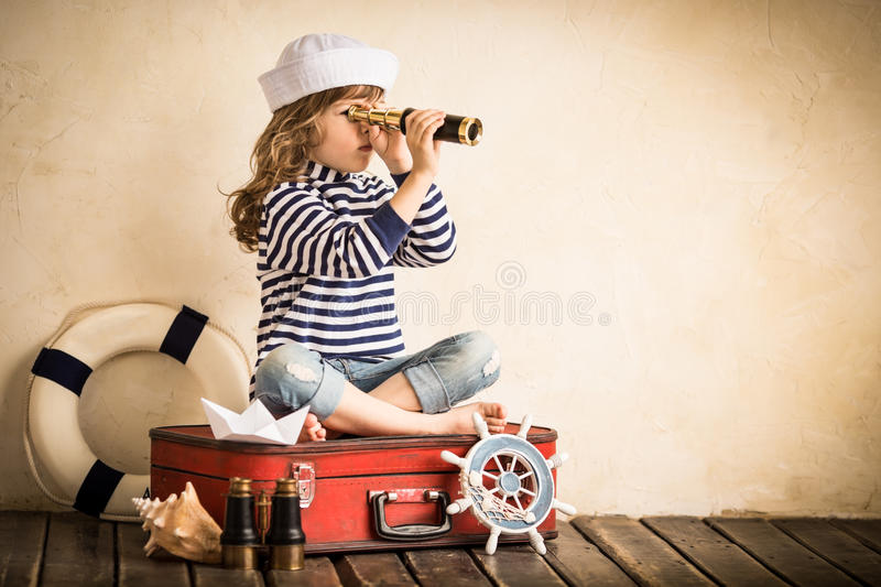 Adventure. Happy kid playing with toy sailing boat indoors. Travel and adventure concept royalty free stock photos