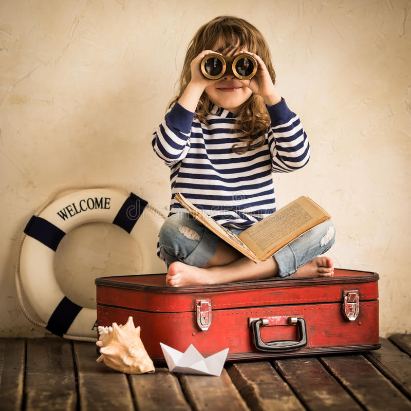 Adventure. Happy kid playing with toy sailing boat indoors. Travel and adventure concept stock photos