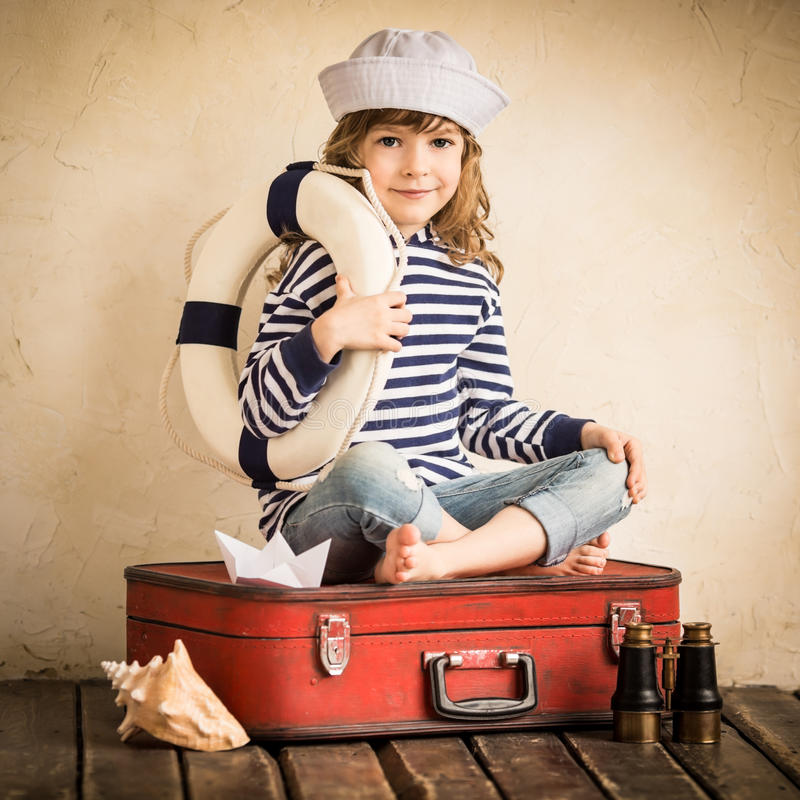 Adventure. Happy kid playing with toy sailing boat indoors. Travel and adventure concept royalty free stock photography