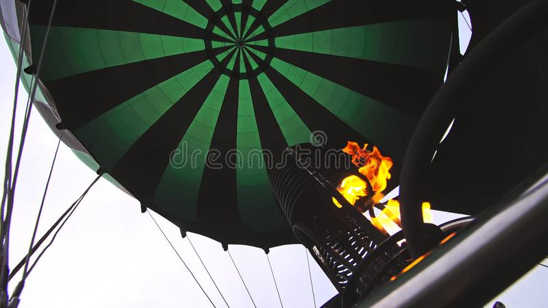 Adventure on hot air balloon watermelon. Burner directing flame into envelope. The aircraft fly in morning blue sky due royalty free stock image