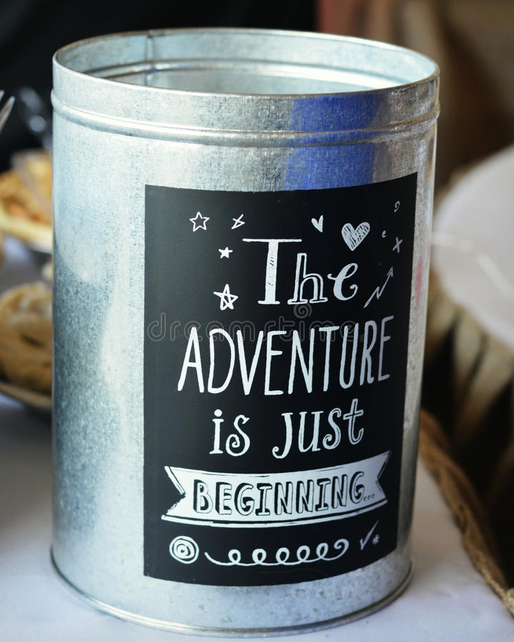 The Adventure is Just Beginning. A tin can with a chalkboard sticker on it that reads The Adventure is Just Beginning in chalk. Wedding Decoration royalty free stock image