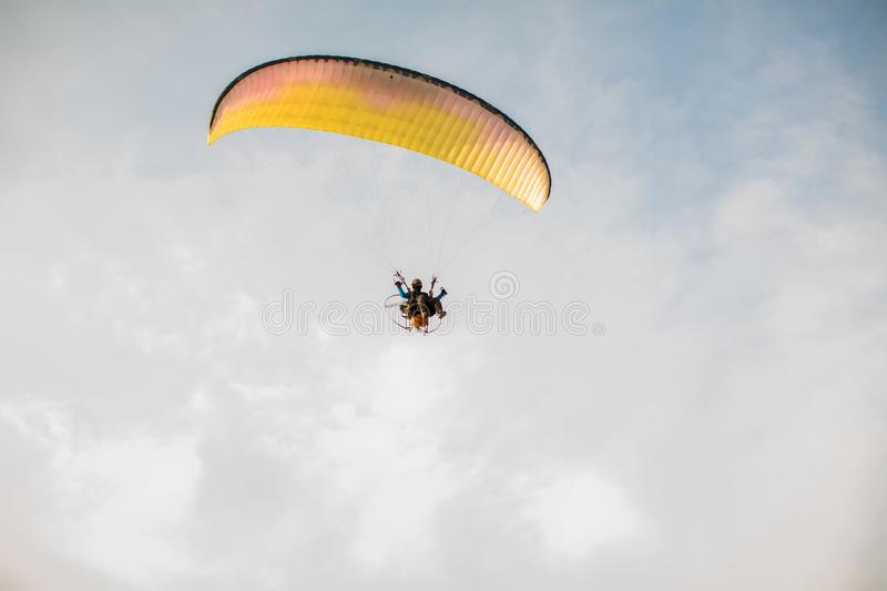 Adventure man active extreme sport pilot flying in sky with paramotor engine glider parachute. royalty free stock photos