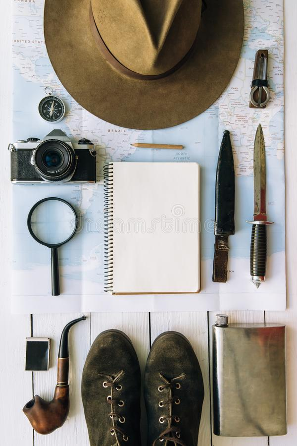 Adventure planning flat lay. Travel vintage gear on map. Including boots, smoking pipe, hat, notepad. Exploring, hiking empty royalty free stock photo