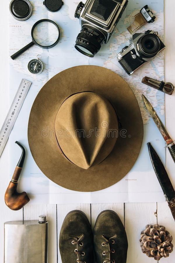 Adventure planning flat lay. Travel vintage gear on map. Including film camera, hat, knife, loupe, compass. Exploring, hiking stock photos