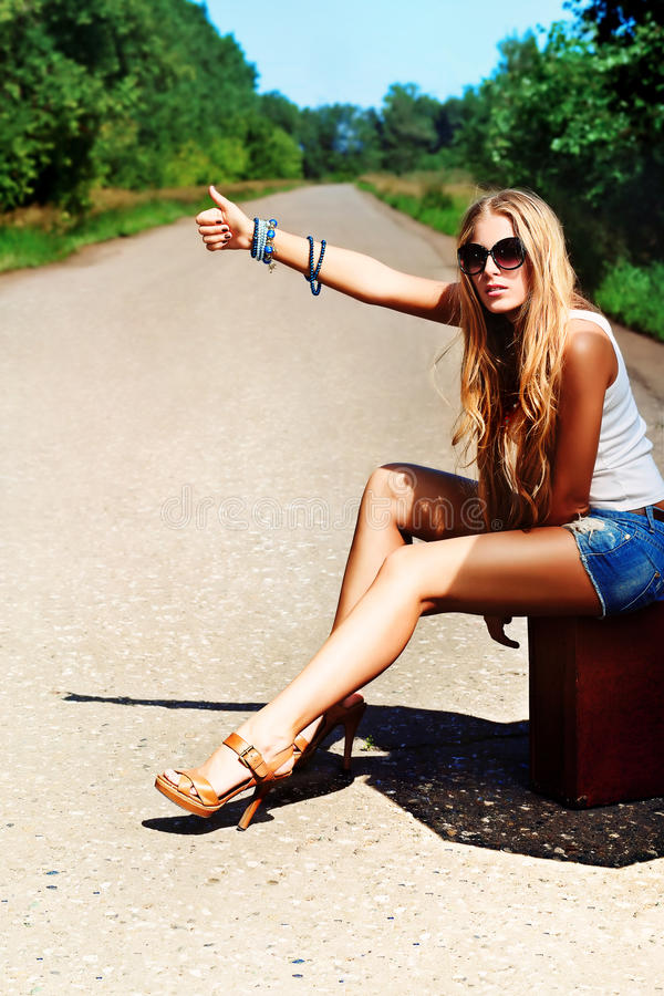 Adventure road. Pretty young woman hitchhiking along a road royalty free stock image