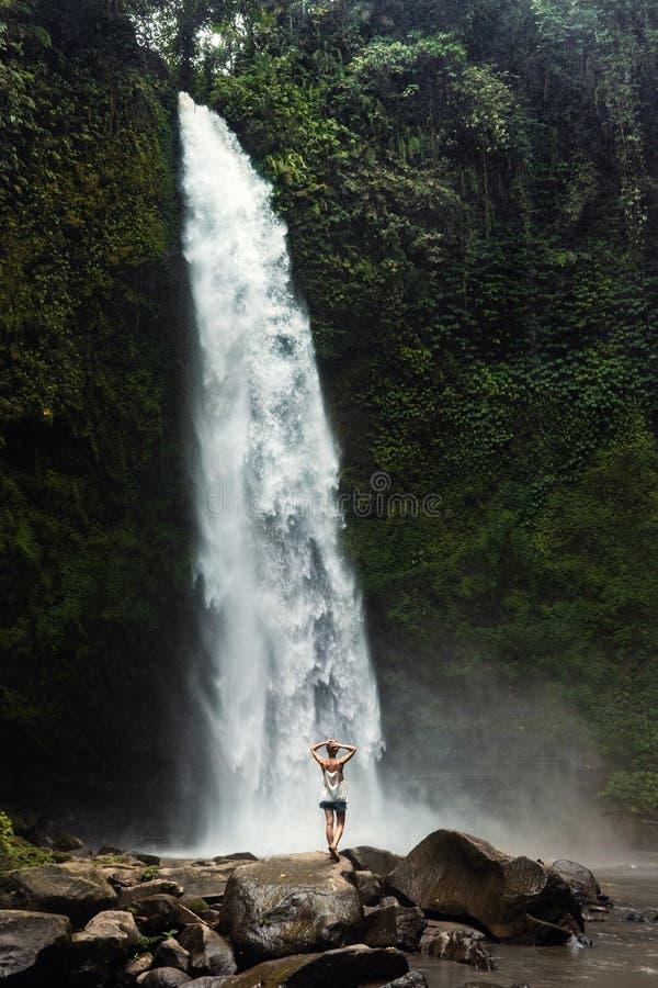 Adventure seeker at beautiful jungle waterfall. And enjoying nature royalty free stock photo