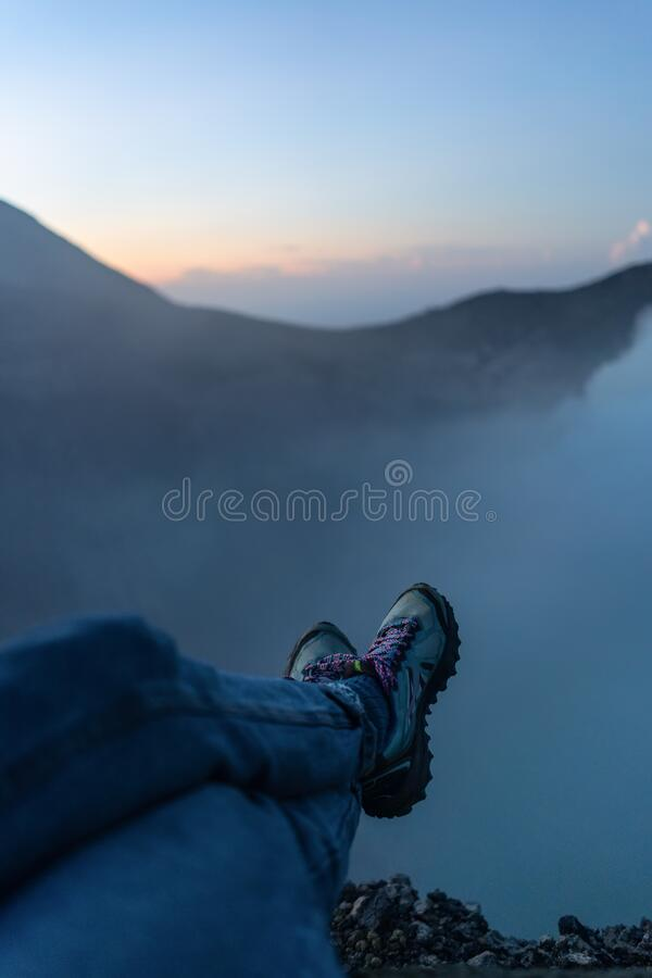 Adventure seeker sitting on the cliff and enjoying the view. Of acid lake in Ijen volcano crater at sunrise stock photography