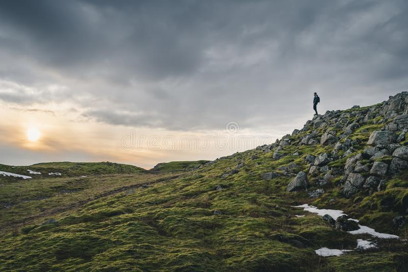 Adventure seeker, young traveler and outdoor soul in the wilderness of Iceland during the midnight sun or sunset staying on the royalty free stock photography