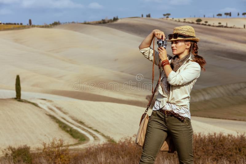 Solo traveller woman taking photos with retro photo camera. Adventure solo traveller woman in hiking clothes with bag taking photos with retro photo camera on stock image