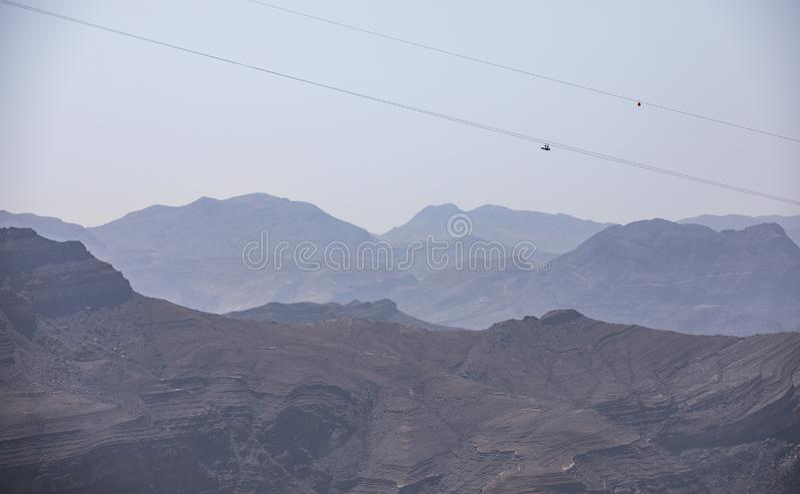 Adventure sport - zipline slide down Jebel Jais mountain. Two people sliding down Jebel Jais Mountain via world`s longest zip line stock photos