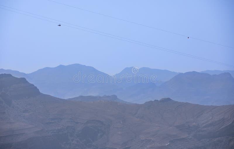 Adventure sport - zipline slide down Jebel Jais mountain. Two people sliding down Jebel Jais Mountain via world`s longest zip line stock photography