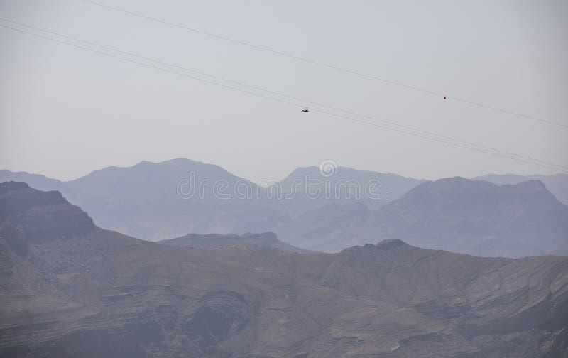 Adventure sport - zipline slide down Jebel Jais mountain. Two people sliding down Jebel Jais Mountain via world`s longest zip line royalty free stock images