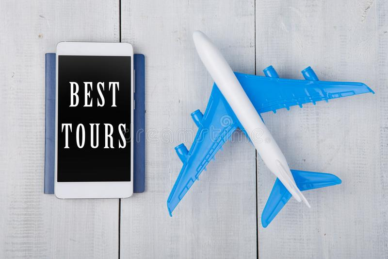 plane, passport and smartphone with text & x22;Best Tours& x22; on white wooden table stock photos