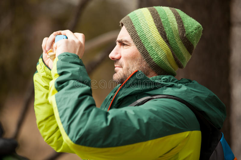 Adventure tourist man taking a picture. Hiking royalty free stock images