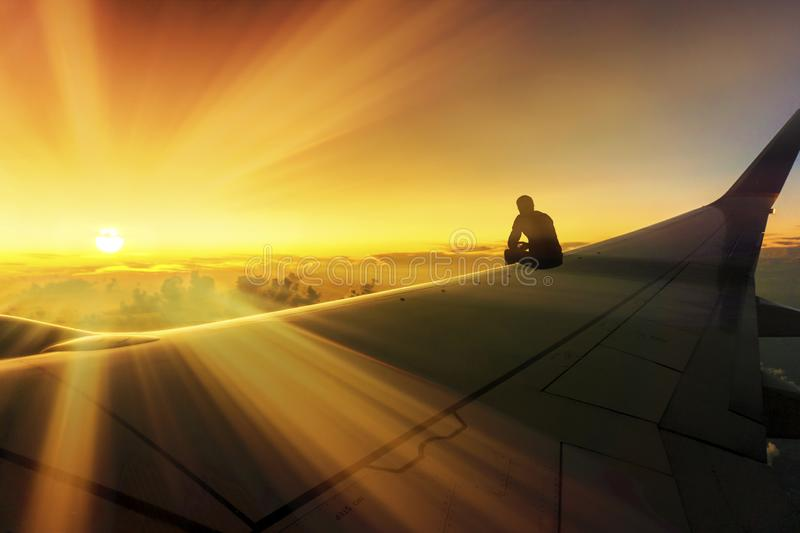 Adventure Travel Conceptual Photo of Silhouette of Man Sitting on Airplane Wing Watching Stunning Sunset World Destination royalty free stock photo