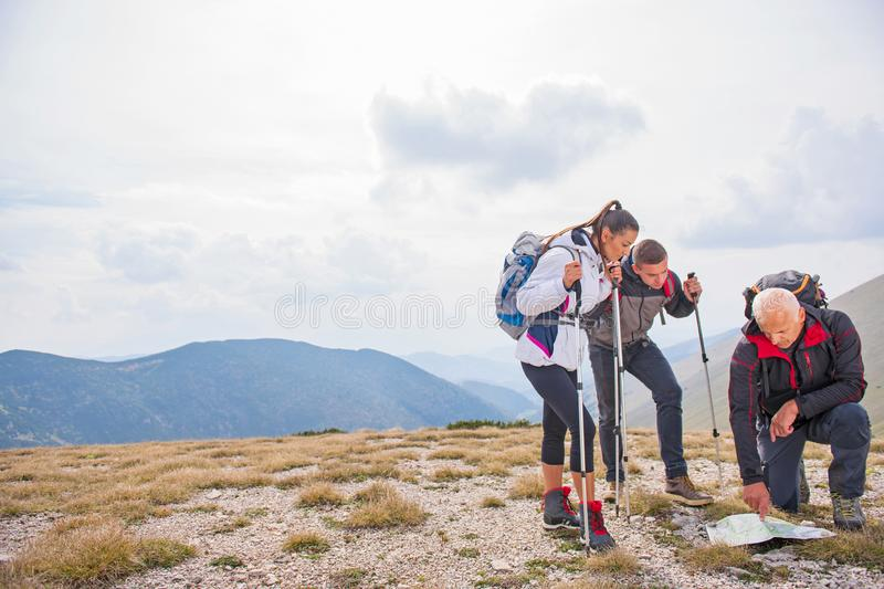 Adventure, travel, tourism, hike and people concept - group of smiling friends with backpacks and map outdoors royalty free stock photography