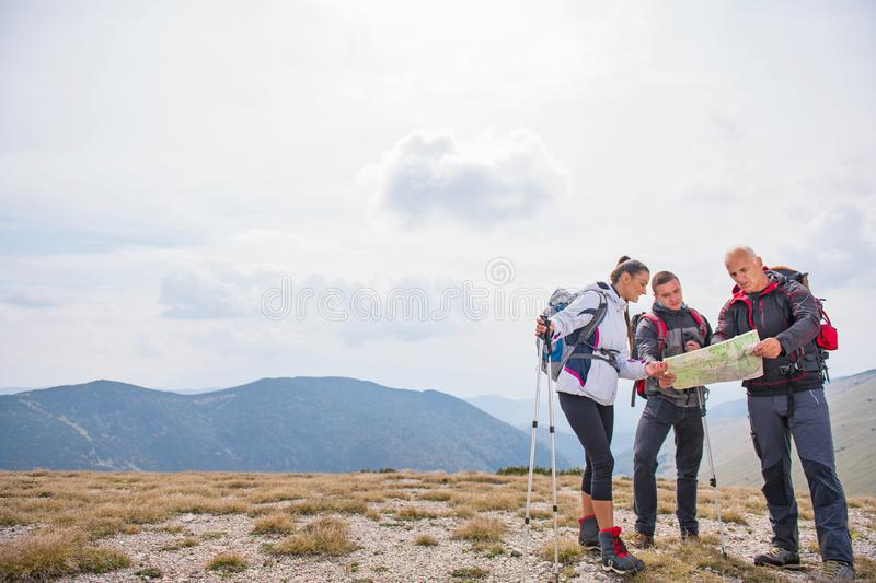 Adventure, travel, tourism, hike and people concept - group of smiling friends with backpacks and map outdoors royalty free stock image