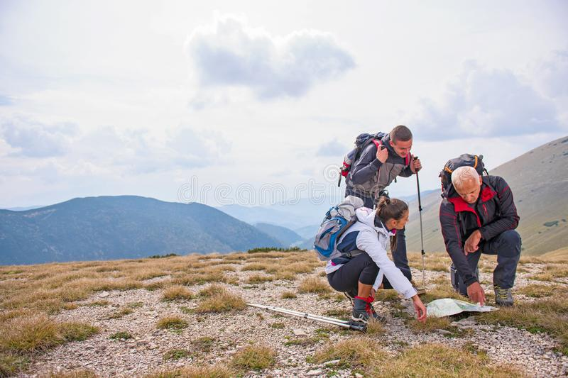 Adventure, travel, tourism, hike and people concept - group of smiling friends with backpacks and map outdoors royalty free stock images