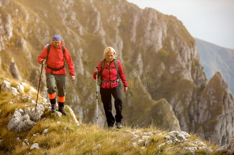 Adventure, travel, tourism, hike and people concept - smiling couple walking with backpacks outdoors royalty free stock photography