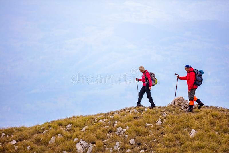 Adventure, travel, tourism, hike and people concept - smiling couple walking with backpacks outdoors royalty free stock photo