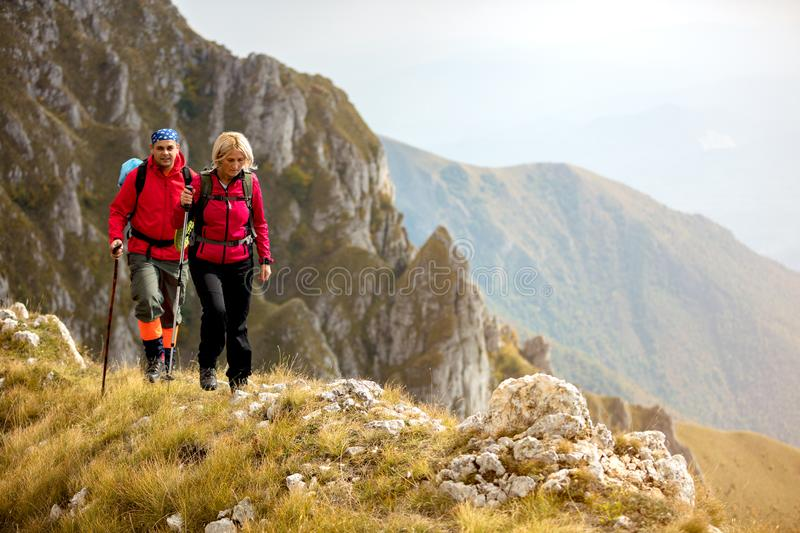 Adventure, travel, tourism, hike and people concept - smiling couple walking with backpacks outdoors stock image