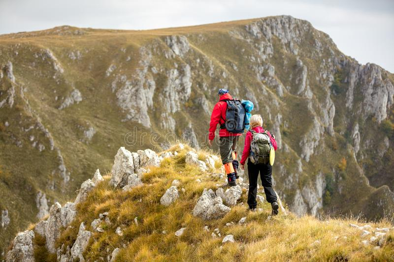 Adventure, travel, tourism, hike and people concept - smiling couple walking with backpacks outdoors stock images