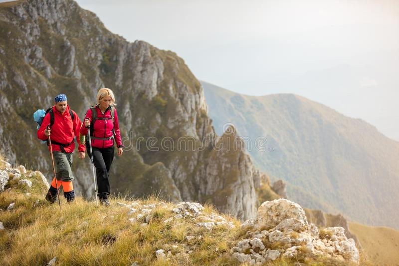 Adventure, travel, tourism, hike and people concept - smiling couple walking with backpacks outdoors.  stock images