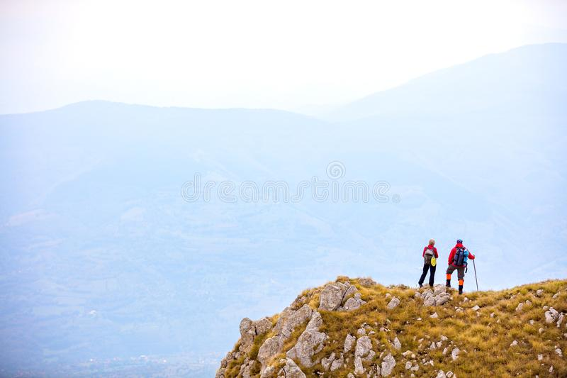 Adventure, travel, tourism, hike and people concept - smiling couple walking with backpacks outdoors royalty free stock image